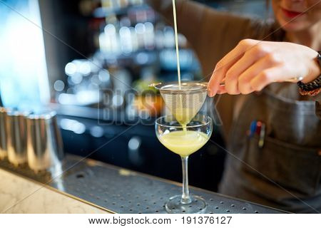 alcohol drinks, people and luxury concept - woman bartender poring cocktail through strainer into glass at bar