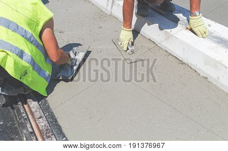 Construction worker leveling concrete pavement outdoors with trowels.
