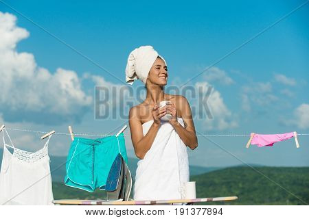girl or happy housewife in terry towel hold coffee tea cup near iron and ironing board at underwear hang on clothesline rope on clothespin sunny outdoor on cloudy blue sky background