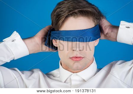 businessman blindfolded with tie in white shirt on blue background