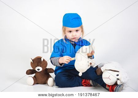 doctor kid or small boy in blue uniform playing vet with toy animal of donkey and bear in medical hospital isolated on white background medicine and healthcare copy space