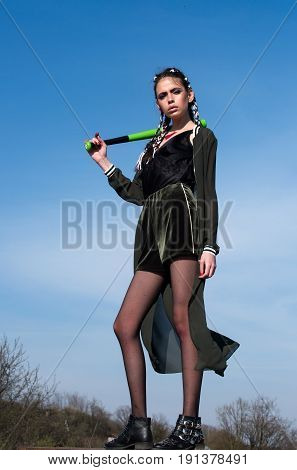 baseball bat in hand of young woman or model on blue sky