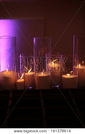 Romance Beautiful candles burning in elegant glass candleholders of different sizes on wooden board on glowing background. Home decor. Holidays celebration. Dark and light. Heat energy
