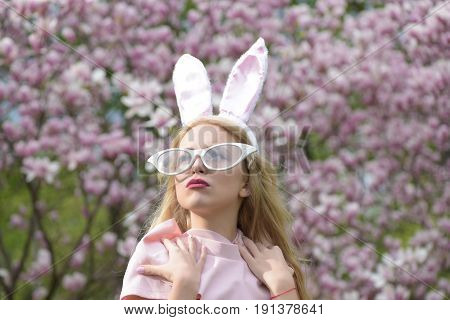 Pretty girl or cute woman fashionable model with bunny ears and funny glasses with long blond hair posing in pink top at blossoming trees in park on blurred floral environment. Easter. Spring