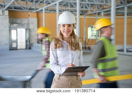 Mature Contractor In Helmet Making Notes At Clipboard And Looking At Camera