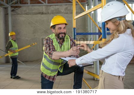 Mature Foreman In Builder Uniform Talking With Contractor On Construction Site