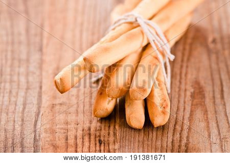 Group of bread sticks on wooden table.