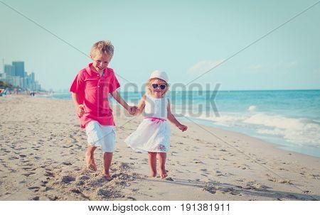 happy little boy and girl running on beach