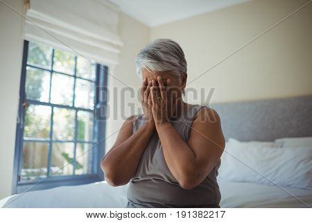 Upset senior woman covering her face at home
