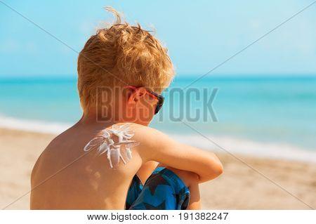 sun protection- little boy with suncream on shoulder on tropical beach