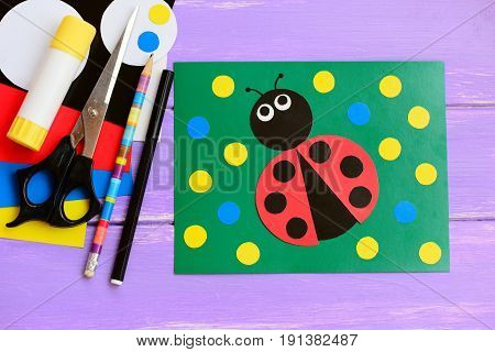 Bright ladybug cardboard card. Green card with ladybug, scissors, glue stick, pencil, marker, cardboard set on a wooden table. Summer homemade card idea to make. Closeup