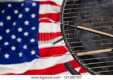 Close-up of tong arranged on barbeque against American flag