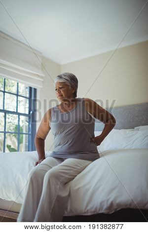 Senior woman suffering from back pain while sitting on bed at home