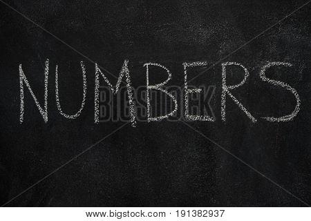 Numbers word written with chalk on blackboard. Education, school concept