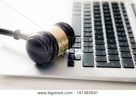 Wooden gavel on laptop keyboard. auction online law technology justice concept