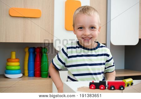 Child Boy Play With Wooden Train In Kindergarten