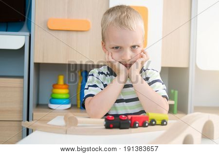 Bored Sad Little Boy Sitting At Table