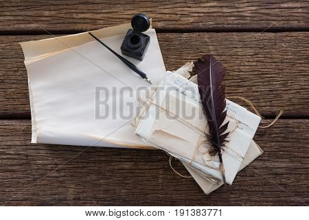 Quill feather, ink bottle, ink pen and legal documents arranged on wooden table