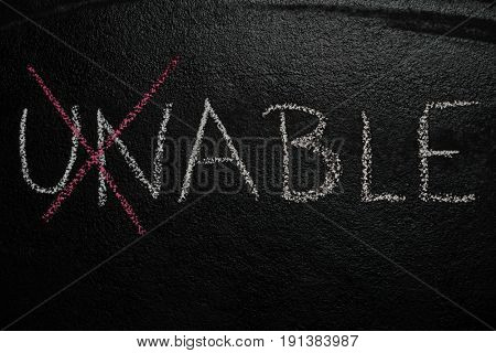 Cross over unable word drawn with chalk on blackboard. The unable is able concept