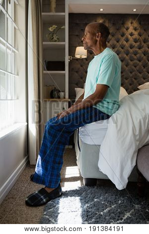 Side view of senior man looking out though window while sitting on bed at home