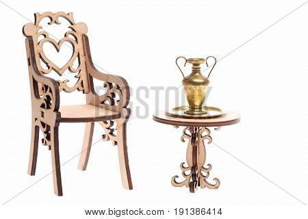 golden jug on tray on wooden table with decorative chair isolated on white background