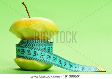 Flexible Ruler In Cyan Color Ties Around Bitten Apple