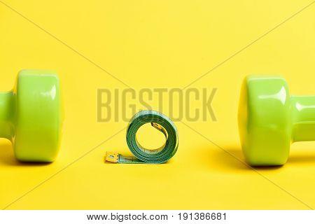 Roll Of Cyan Measuring Tape Between Pair Of Green Dumbbells