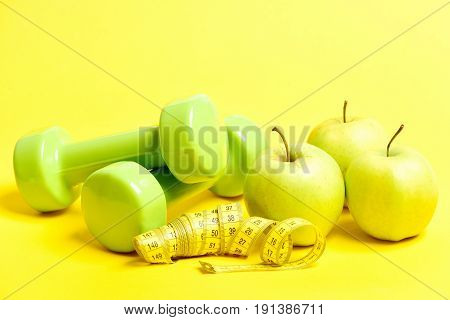 Tube Of Measuring Tape On Yellow Color, Several Apples