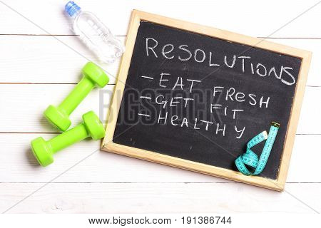 Chalkboard with resolutions: eat fresh get fit and healthy on white wooden background near green dumbbells and bottle of water with cyan blue measuring tape on board top view. Fitness plan concept