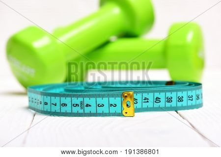 Cyan Measuring Tape In Big Roll And Green Dumbbells