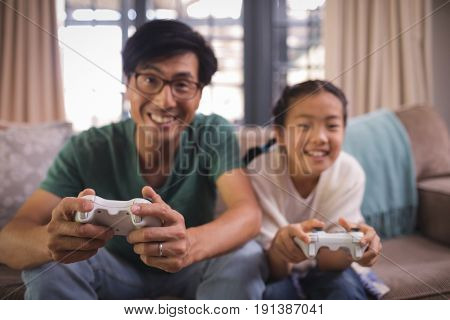 Father and daughter playing video game in living room at home
