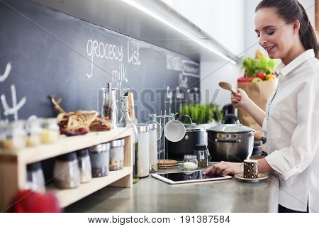 Young woman standing by the stove in the kitchen . Woman cooking