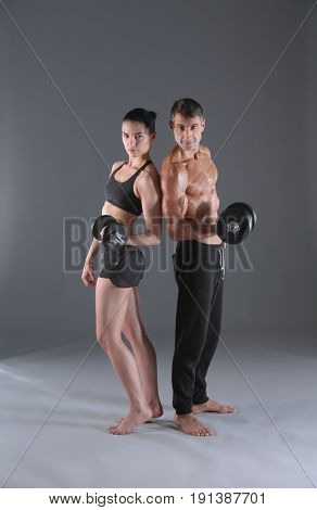 Athletic man and woman with a dumbells. Personal fitness instruc