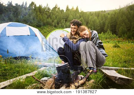 Portrait of happy couple sitting near by the campfire with the tents on background Montenegro