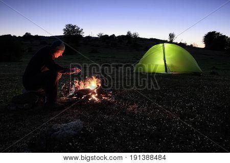 man heats on the campfire near the illuminated tent at dusk in Nebrodi Park, Sicily
