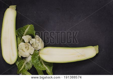 Composition on dark background organic vegetarian foods: green leafy vegetables, zucchini, cauliflower. The view from the top. place for text