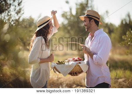 Happy young couple holding wicket basket while standing together at olive farm
