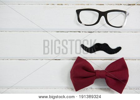 Close up of eyeglasses and bow tie arranged with mustache on wooden table