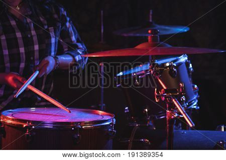 Mid section of female drummer playing drum set in nightclub