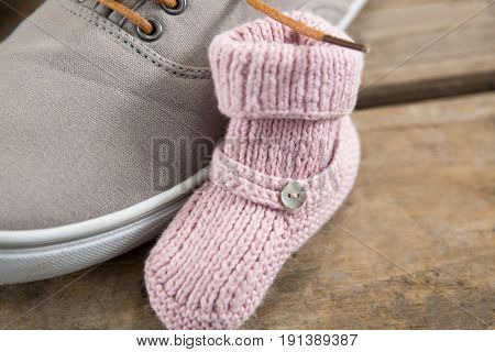 Close up of shoe with baby booties on wooden floor