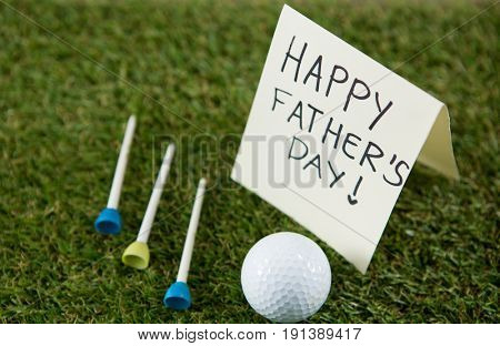 Close up of greeting card with happy fathers day text by golf ball and tees on grassy field