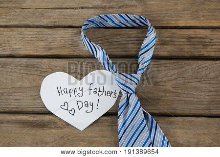 High angle view of heart shape paper with text by necktie on wooden table