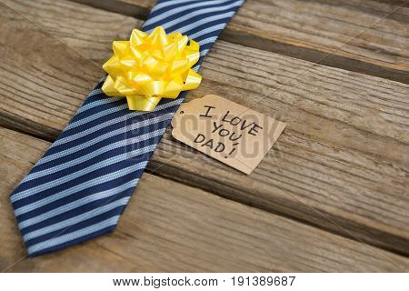 High angle view of necktie with greetings on wooden table