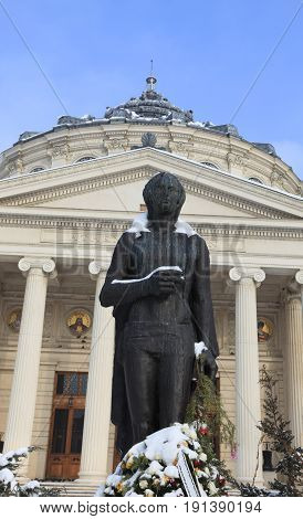 Image of the George Enescu's statue during the winter season in front of the Romanian Atheneum building in BucharestRomania.