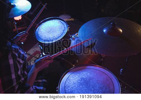 Mid section of drummer playing drum kit in nightclub