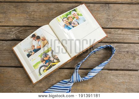 Overhead view of photo album by necktie on wooden table