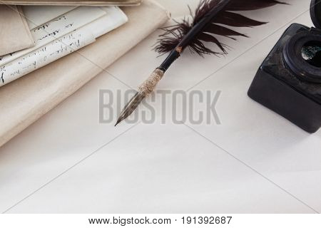 Close-up of quill feather, ink bottle and legal documents arranged on white background