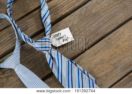 Overhead view of neckties with fathers day message on wooden table