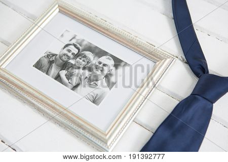 High angle view of picture frame by necktie on white table