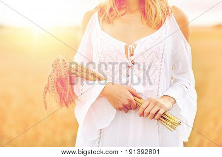 country, nature, summer holidays, vacation and people concept - close up of smiling young woman in white dress with spikelets on cereal field